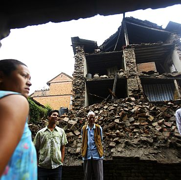 Residents survey damaged buildings a day after a magnitude 6.8 earthquake struck Nepal, India and Bangladesh, at Bhaktapur in Nepal