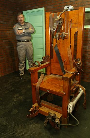 Aaron Dickson, President of the Board of Directors of the Texas Prison Museum stands Old Sparky, the Texas electric chair in which 361 killers were executed. The electric chair is in an exhibit called Riding the Thunderbolt in the non-profit Texas Prison Museum's new facility in Huntsville, Texas
