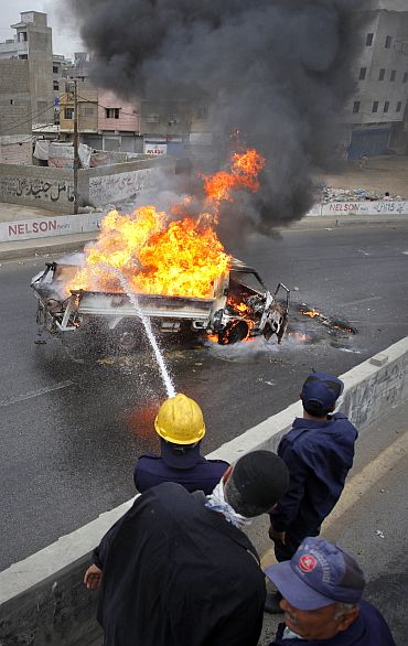 Firefighters extinguish a burning vehicle which was set ablaze by MQM protesters in Karachi