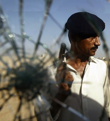 A policeman is seen through the glass of a shattered police van while holding a weapon during a firefight with gang members on the streets of Karachi