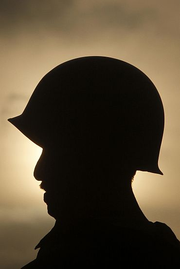 A soldier from Pakistan's paramilitary Rangers is silhouetted against the rising sun as he stands guard in the Lyari area of Karachi