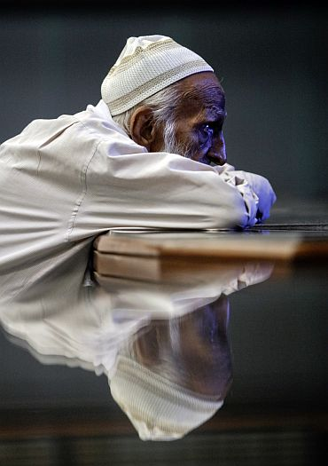 An old man leans over a marble table in a shop in Karachi