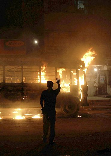 A policeman asked residents to stay in their homes after supporters of Muttahida Qaumi Movement torched a bus early in protest of the killing of a member of party in Karachi