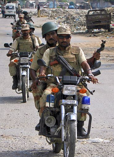 Pakistani Rangers security forces carry weapons on their motorbikes as they patrol the streets of Karachi