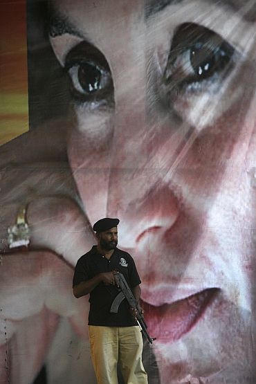 A policeman stands guard along a road for a passing politician in front of a image of late Prime Minister Benazir Bhutto in Karachi
