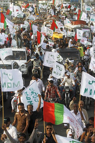 Supporters of Muttahida Qaumi Movement wave party and peace flags during a government sponsored peace rally in Karachi