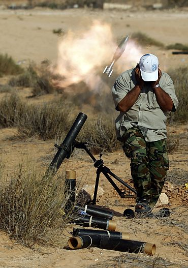 An anti-Gaddafi fighter fires a mortar against loyalists near Sirte