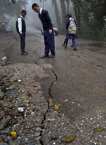 Schoolboys stop to look at a crack running down a road following the earthquake in Gangtok