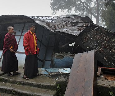 Young monks walk past a damaged house after the earthquake in Gangtok