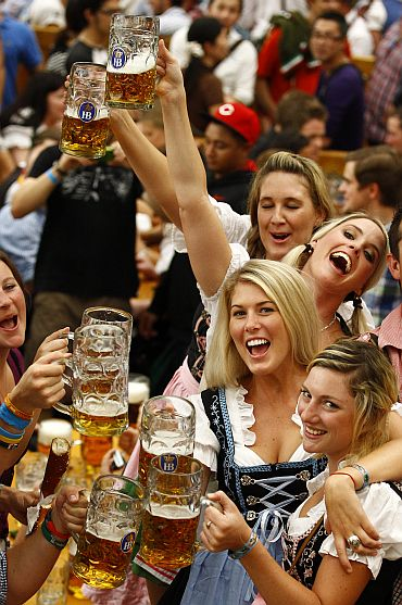 Revellers toast with the traditional 1-litre beer mugs at the opening of the Munich Oktoberfest