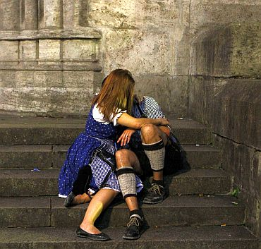 Revellers wearing traditional Bavarian clothes hug on the stairs of the St Peter and Paul church after leaving the Munich Oktoberfest, in Munich