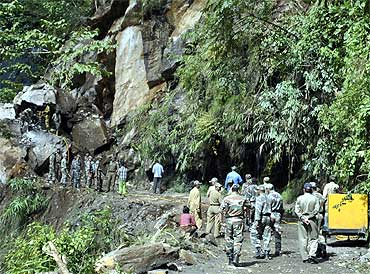 Army personnel work to clear a road blocked by landslide, which was caused by Sunday's earthquake, at Mangan village
