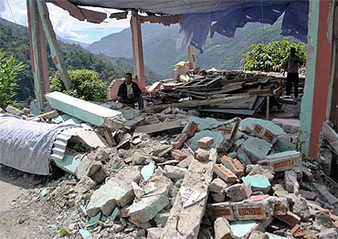 A man sits amid the rubble of a building which was destroyed by Sunday's earthquake at Rangrang village