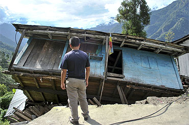 A man stands in front of his house, which was damaged by Sunday's earthquake, at Mangan village