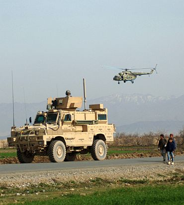 US soldiers provide security for Afghan National Security Forces (ANSF) Mi-17 Hip helicopters as they prepare to land during a training mission in Khanjarkhe, Afghanistan