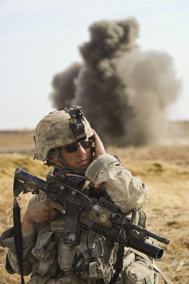 A US soldier takes cover from shelling