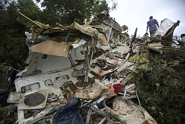 Nepalese police personnel are seen at the crash site of Buddha Air plane in Lalitpur