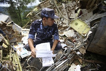 A Nepalese policeman is seen at the crash site of Buddha Air plane in Lalitpur