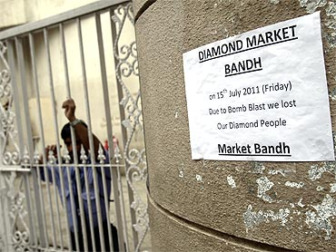 A private security guard stands next to a sign that reads 'Diamond market shut' at Opera House