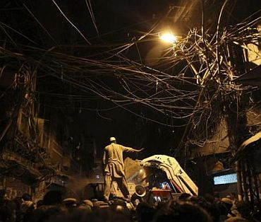 A man directs a bulldozer as he stands under a cluster of overhead wires at the site of the collapsed building