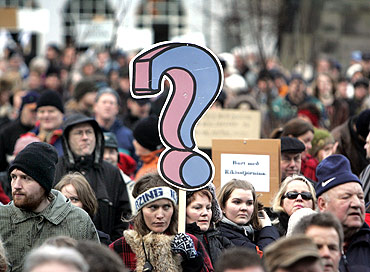 A woman holds a placard during a peaceful protest near Iceland's Parliament house in Reykjavik