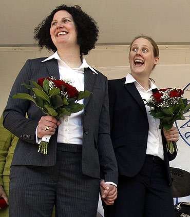 A couple smile during their wedding ceremony at Humlegarden park in Stockholm