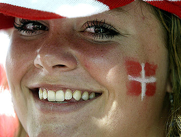 A Danish fan with a painted face smiles before a match