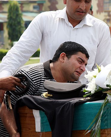 A relative weeps on the coffin of the young officer