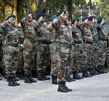 Indian Army officers salute during a wreath laying ceremony for the late Lieutenant Sushil Khajuria, in a military garrison in Srinagar