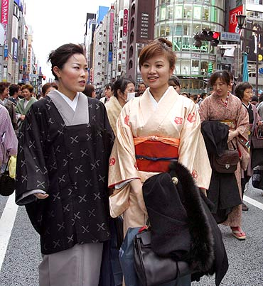 Kimono-clad women walk across a street during an event at Tokyo's Ginza shopping district