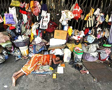 A woman sleeps in front of her belongings, hanging from the shutters of a shop, in Kolkata