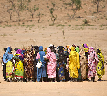 Women who fled fighting in eastern Chad gather around members of a delegation from the UNSC