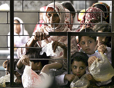Women and children wait for free food at the shrine of Muslim Saint Data Ganj Bakhsh in Lahore