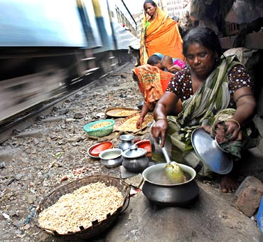 A woman cooks using a makeshift stove in a slum as a train passes by in Dhaka