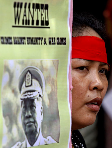 A woman holds a placard during a protest against Myanmar's military ruler Than Shwe