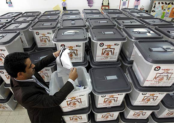 A Jordanian election official checks a ballot box at a public school used as a temporary vote counting centre