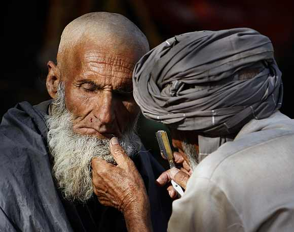 A street barber nicks the face of a man as he gives him a shave in Kabul
