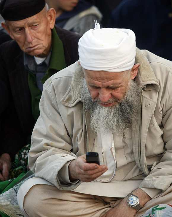 A man looks at a mobile phone as he attends special prayers