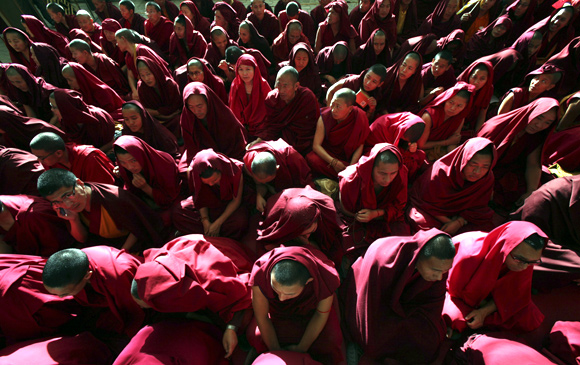 Tibetan monks wait for the body of Jampel Yeshi inside the Tsuglagkhang temple in Dharamsala