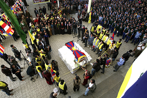 Tibetan exiles gather around the coffin containing the body of Jampel Yeshi inside the Tsuglagkhang temple