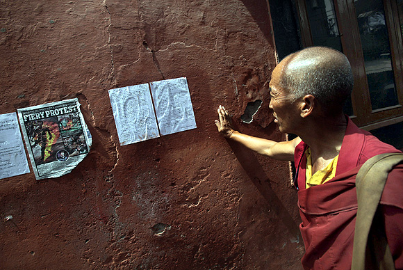 A Tibetan exile reads a note written by Jamphel Yeshi before his final protest against China