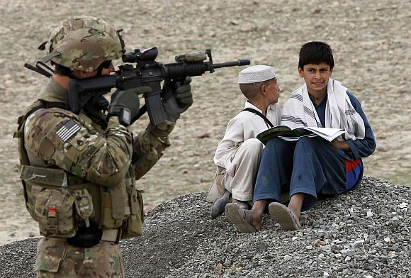 Afghan residents sit on the ground near a US army soldier securing the perimeter of a government building in Laghman province
