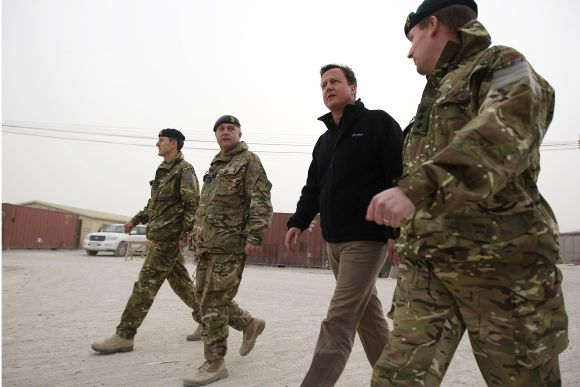 Britain's Prime Minister David Cameron walks through Kandahar airfield during a visit to meet British forces in Afghanistan
