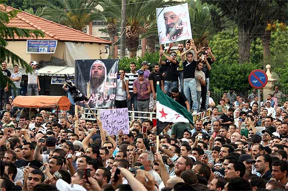 Protesters hold a poster of Osama bin Laden
