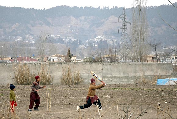 Children play cricket near the boundary wall of the building where Al Qaeda leader Osama bin Laden was killed