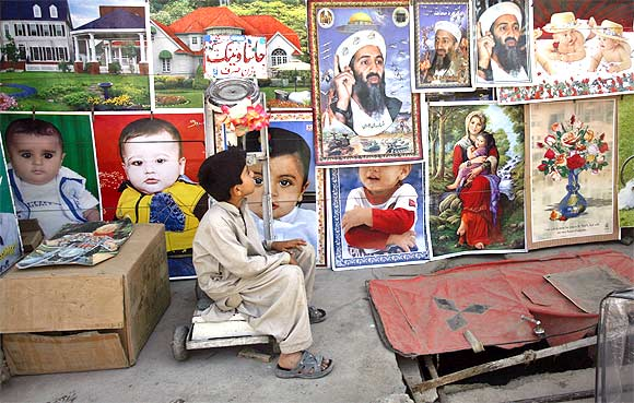 A child looks up at posters depicting slain Al Qaeda leader Osama bin Laden at a roadside stall in Quetta