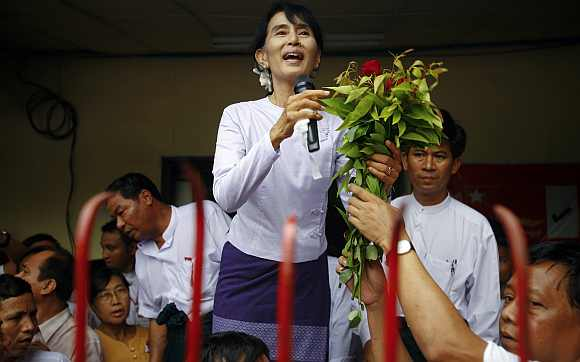 Myanmar's pro-democracy leader Aung San Suu Kyi receives flowers as she addresses supporters and reporters from the NLD office in Yangon