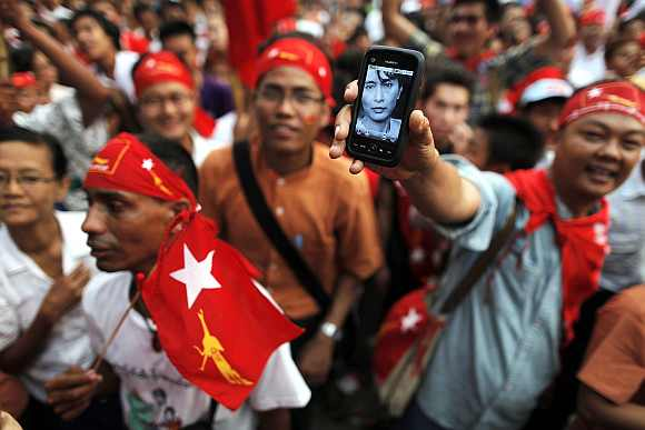 A man shows a phone with a picture of Aung San Suu Kyi in front of the head office of the National League for Democracy in Yangon