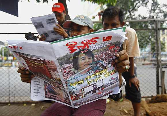 Locals read a journal on a walkway in Yangon about Suu Kyi's win
