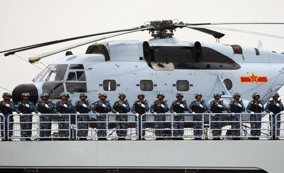 Chinese marines aboard a naval ship with a Changhe Z-8 helicopter during a ceremony in Qingdao